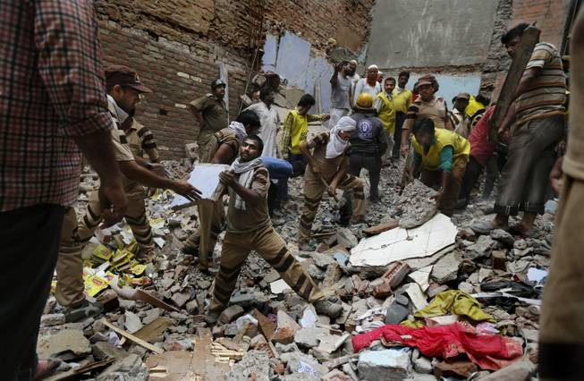 Rescue workers clear debris at the site of a building collapse in New Delhi, India, on Saturday, June 28, 2014. A dilapidated building collapsed in the Indian capital, killing at least 15 people.