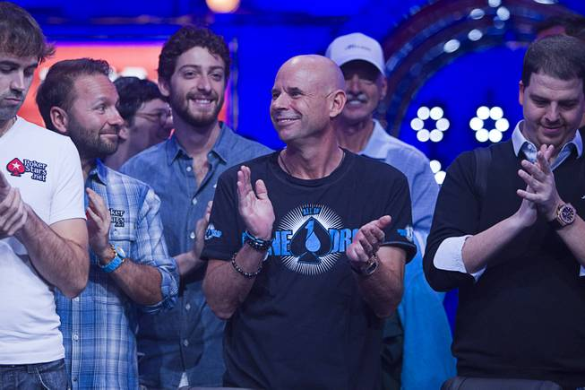 Poker players, including Cirque du Soleil cofounder Guy Laliberte, center, applaud during opening ceremonies before the start of the Big One for One Drop, a $1,000,000 buy-in No-Limit Hold'em charity poker tournament, at the Rio Sunday, June 26, 2014. The $1 million buy-in is the largest ever for a poker event. Proceeds support One Drop projects in countries experiencing serious difficulties caused by inadequate access to water.