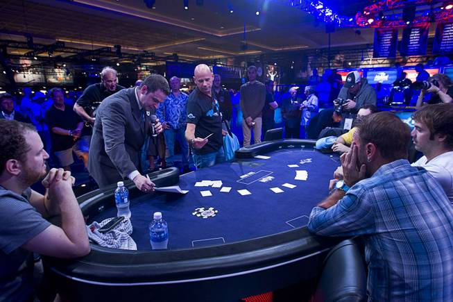 Cirque du Soleil cofounder Guy Laliberte, center, selects his seat before the start of the Big One for One Drop, a $1,000,000 buy-in No-Limit Hold'em charity poker tournament, at the Rio Sunday, June 26, 2014. The $1 million buy-in is the largest ever for a poker event. Proceeds support One Drop projects in countries experiencing serious difficulties caused by inadequate access to water.