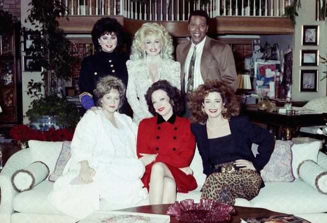 "Actor Meshach Taylor, top right, joins the cast of ""Designing Women"" and special guest Dolly Parton, top center, for the taping of the New Year's Day episode of the show Dec. 8, 1989, in Burbank, California. Taylor's agent says the actor, who appeared in the hit sitcoms ""Designing Women"" and ""Dave's World"" died of cancer on Saturday, June 28, 2014, at his home in Los Angeles. He was 67."