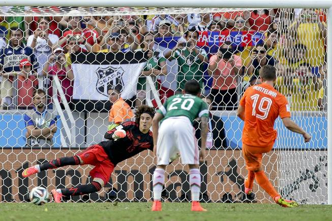 Mexico's goalkeeper Guillermo Ochoa can not stop a penalty shot by Netherlands' Klaas-Jan Huntelaar to score his side's second and winning goal during the World Cup round of 16 soccer match between the Netherlands and Mexico at the Arena Castelao in Fortaleza, Brazil, Sunday, June 29, 2014. The Netherlands defeated Mexico 2-1. (AP Photo/