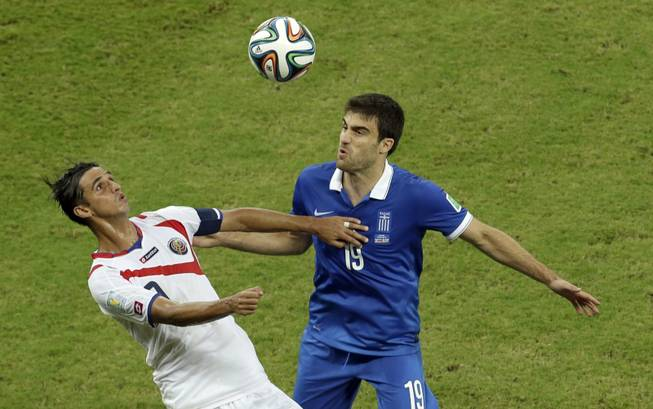 Costa Rica's Bryan Ruiz, left, and Greece's Sokratis Papastathopoulos challenge for the ball during the World Cup round of 16 soccer match between Costa Rica and Greece at the Arena Pernambuco in Recife, Brazil, on Sunday, June 29, 2014.