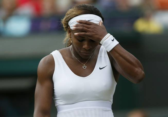 Serena Williams of the U.S. gestures after losing a point to Alize Cornet of France during their women's singles match at the All England Lawn Tennis Championships in Wimbledon, London, Saturday, June 28, 2014.