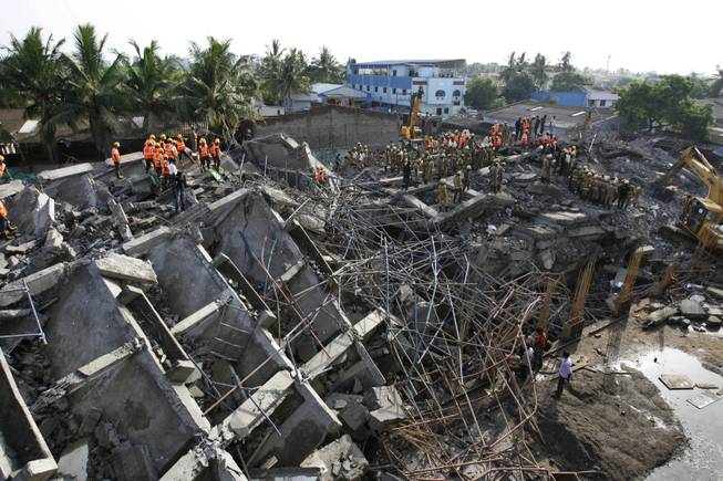 Rescuers search for workers believed buried in the rubble of a building that collapsed on the outskirts of Chennai, India, Sunday, June 29, 2014. The 12-story apartment structure the workers were building collapsed late Saturday while heavy rains and lightning were pounding. Police said 31 construction workers had been pulled out so far and the search was continuing for more than a dozen others.