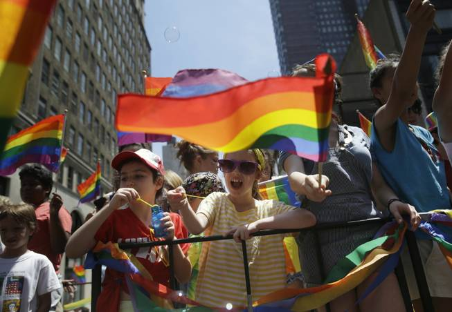 Children blow bubbles as they pass by on a float in the Gay Pride Parade in New York on Sunday, June 29, 2014. Fifth Avenue became one big rainbow on Sunday, as thousands of participants waving multicolored flags made their way down the street for New York City's annual Gay Pride march.