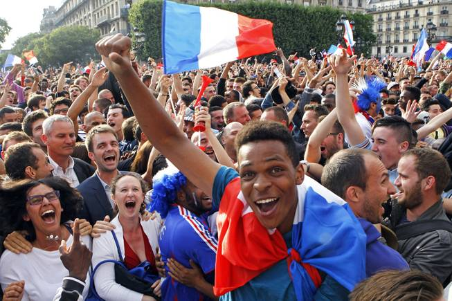 French soccer fans celebrate after France scored the first goal, as they watch the World Cup soccer match between France and Nigeria being shown live on a giant screen, in front of Paris City Hall, Monday June 30, 2014. France won the match 2-0, played at the Estadio Nacional stadium in Brasilia, Brazil.