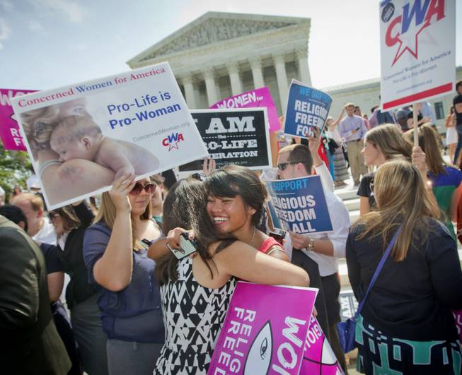 Demonstrators embrace as they react to hearing the Supreme Court's decision on the Hobby Lobby case outside the Supreme Court in Washington, Monday, June 30, 2014. The Supreme Court says corporations can hold religious objections that allow them to opt out of the new health law requirement that they cover contraceptives for women.