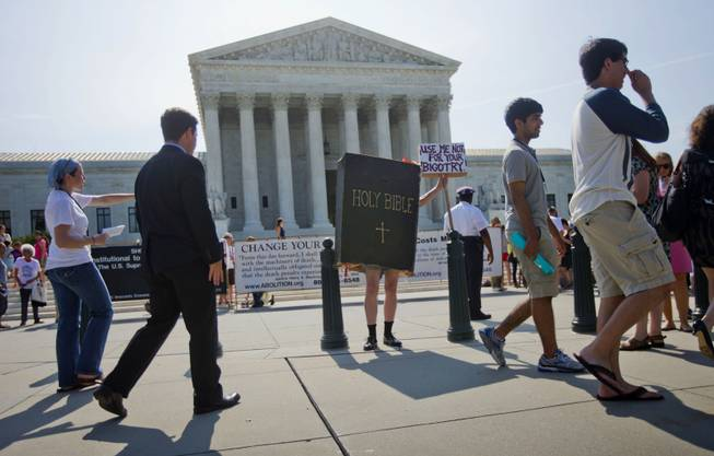 A demonstrator dressed as the 'Bible' stands outside the Supreme Court in Washington, Monday, June 30, 2014, awaiting the court's decision on the Hobby Lobby case. The Supreme Court says corporations can hold religious objections that allow them to opt out of the new health law requirement that they cover contraceptives for women.