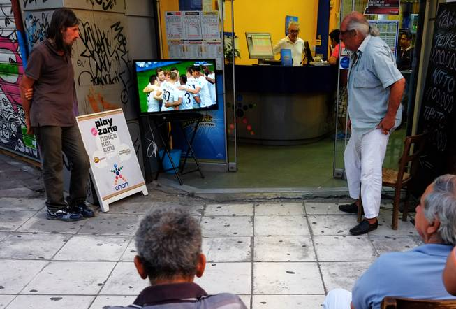People watch the World Cup round of 16 soccer match between France and Nigeria on TV outside of a betting shop in central Athens, Monday, June 30, 2014. France won the match 2-0, played at the Estadio Nacional stadium in Brasilia, Brazil.