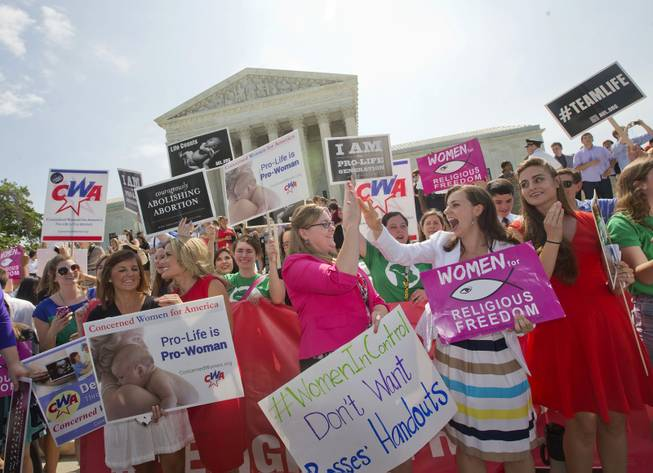 Demonstrator react to hearing the Supreme Court's decision on the Hobby Lobby case outside the Supreme Court in Washington, Monday, June 30, 2014. The Supreme Court says corporations can hold religious objections that allow them to opt out of the new health law requirement that they cover contraceptives for women.