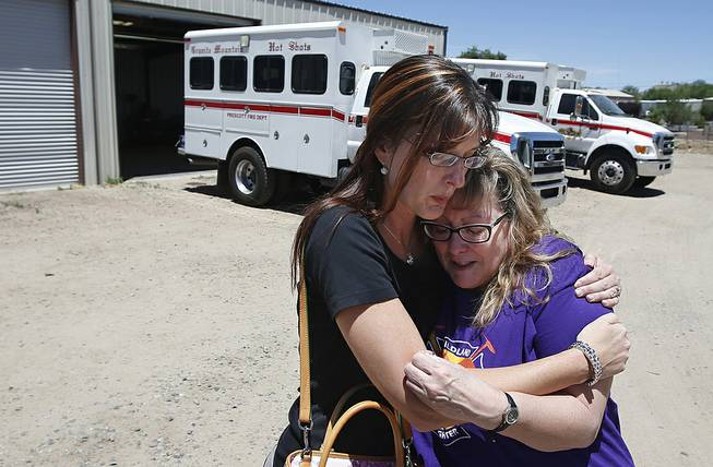 In this Tuesday, June 24, 2014 photo, in her first visit to the firehouse in Prescott, Ariz., since her son's death, Colleen Turbyfill, right, Travis Turbyfill's mother, gets a hug from Katie Cornelius, Prescott Fire Department volunteer exhibit curator for the Tribute Fence Preservation Project, after Turbyfill visited the Granite Mountain Hotshots crew vehicle buggy where her son Travis sat before he was killed along with 18 other hotshots in a wildfire almost a year ago.
