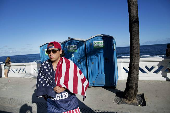 A fan of the U.S. national soccer team walks by the seaside with a U.S. flag draped over his shoulders, in Salvador, Brazil, Monday, June 30, 2014. Salvador is one of the host cities of the FIFA 2014 Soccer World Cup.