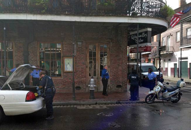 Authorities continue working the scene along Bourbon Street after a shooting, early Sunday, June 29, 2014, in New Orleans. Nine people were shot on Bourbon Street in New Orleans' celebrated French Quarter, leaving at least one person in critical condition.