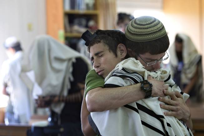 In this Sunday, June 15, 2014, photo, Israeli Jewish religious students hug prior to a prayer at the synagogue where two of the missing Israeli teens studied, in the Jewish settlement of Kfar Etzion.