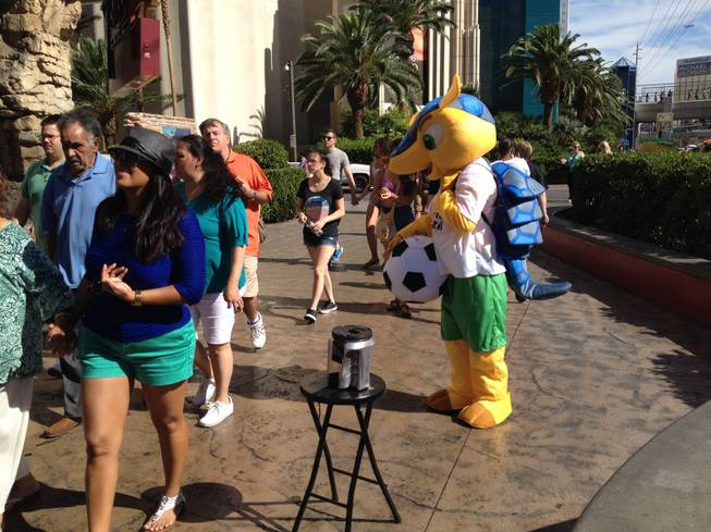 "Street performer Cheikh ""Louis"" Diakhate, dressed as the World Cup mascot Fuleco, is ignored by pedestrians on the Las Vegas Strip on Thursday, June 26, 2014."