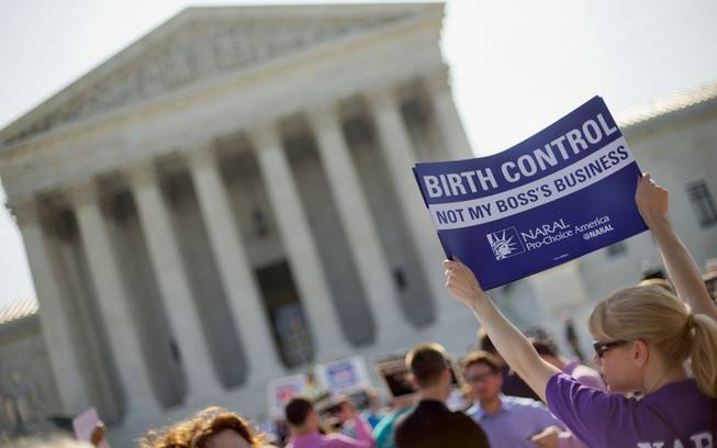 A demonstrator holds up a sign outside the Supreme Court in Washington, Monday, June 30, 2014. The Supreme Court is poised to deliver its verdict in a case that weighs the religious rights of employers and the right of women to the birth control of their choice.