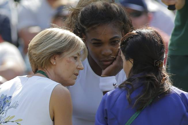 Court officials talk to Serena Williams of the U.S as she and Venus Williams retire after 3 games from their women's doubles match against Kristina Barrois of Germany and Stefanie Voegele of Switzerland at the All England Lawn Tennis Championships in Wimbledon, London, Tuesday July 1, 2014.