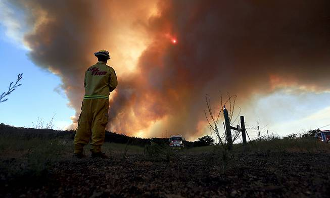 Smoke rises from the Butts Canyon Fire on Tuesday July 1, 2014, near Middletown, Calif., on the border between Lake and Napa counties. Crews are battling a raging wildfire that has burned more than 2,500 acres, damaged five structures and prompted mandatory evacuations.