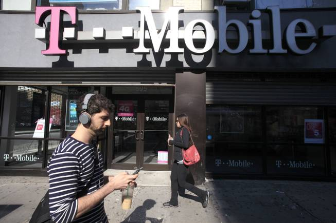 This Sept. 12, 2012, file photo shows a man using a cellphone as he passes a T-Mobile store in New York.