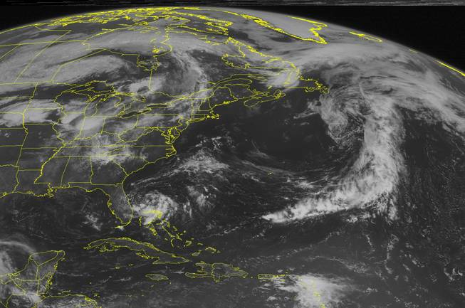 This NOAA satellite image taken Monday, June 30, 2014 at 10:45 AM EDT shows swirl of clouds trying to organize around a center of low pressure that may develop into a tropical depression soon off the eastern Florida Coast with rain and thunderstorms.