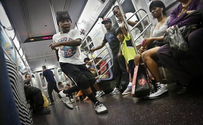 "In this June 17, 2014 photo, Marc Mack, 8, a member with the dance troupe W.A.F.F.L.E., performs on a subway, in New York. Police Commissioner William Bratton's department ""broken window"" crackdown has targeted illegal motorcycles, graffiti and the subway acrobats."