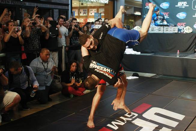 Chris Weidman throws Gian Villante during the open workout for UFC 175 Wednesday, July 2, 2014 at the Fashion Show Mall.