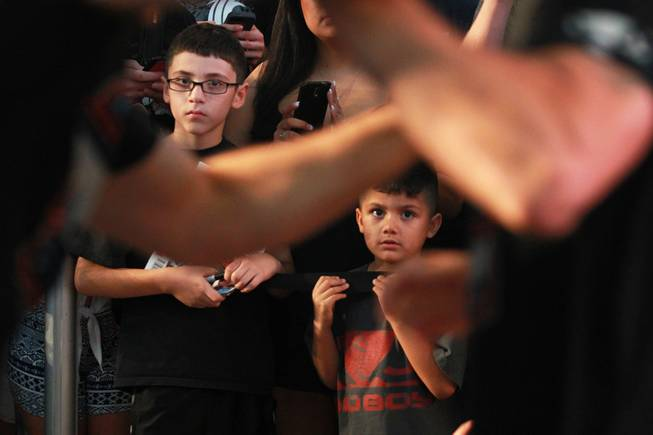 Young fans watch as Chris Weidman loosens up during the open workout for UFC 175 Wednesday, July 2, 2014 at the Fashion Show Mall.