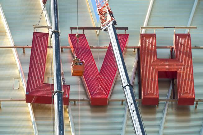 David Siegel, Founder and CEO of Westgate Resorts, is hoisted up over 200 feet to remove the LVH letters off the main sign of Westgate's newly purchased property, Tuesday July 1, 2014.