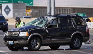 A Las Vegas Metro Police Officer pauses while working the scene of a fatal car crash on the I-15 just north of the I-95 interchange on Wednesday, July 2, 2014.