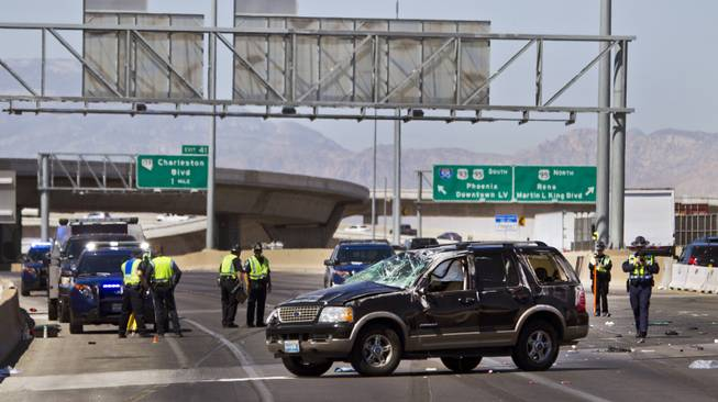 Las Vegas Metro Police continue to work the scene of a fatal car crash on the I-15 just north of the I-95 interchange on Wednesday, July 2, 2014.