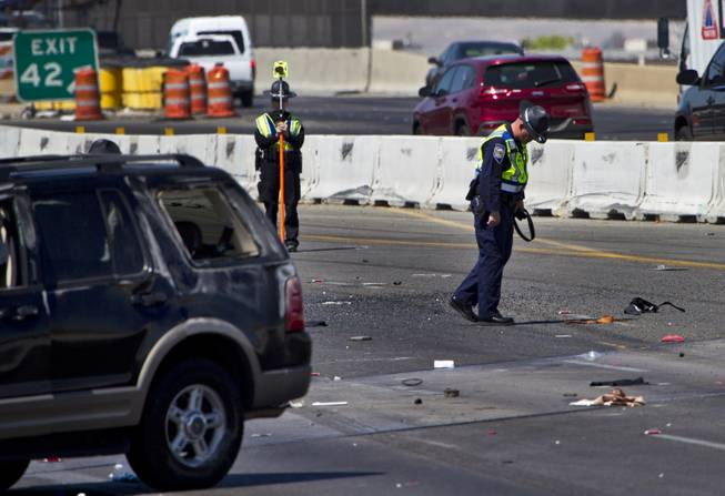 Las Vegas Metro Police continue to document the scene of a fatal car crash on the I-15 just north of the I-95 interchange on Wednesday, July 2, 2014.