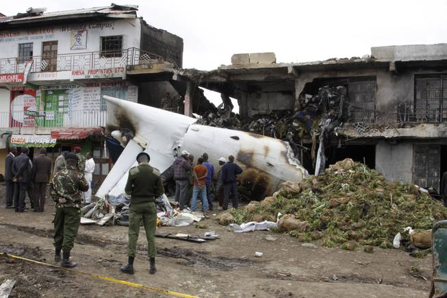 Soldiers and airport staff members look at the wreckage of the Fokker 50 cargo plane after it crashed shortly after takeoff at Kenyatta International Airport, Wednesday, July 2, 2014.