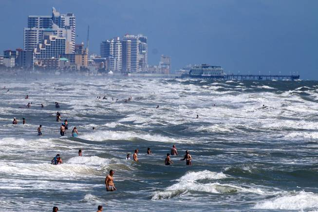 People deal with the high surf and currents off Daytona Beach generated by Tropical Storm Arthur on Tuesday, July 1, 2014.
