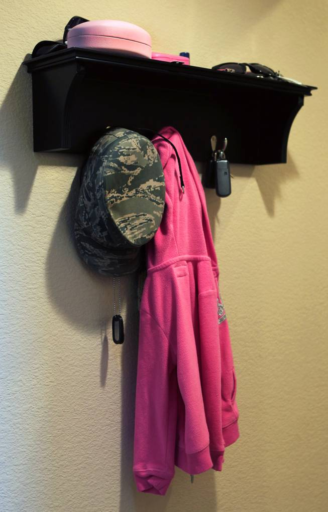 A hat and dog tags belonging to TSGT Rommel Delmundo, currently stationed at Nellis AFB, hang on a small shelf with other family possessions as they ready for another military move Monday, June 16, 2014. L.E. Baskow