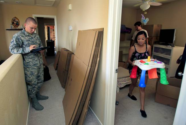 (From right) Rheina Delmundo carries out a small table from her daughter's room as she and family ready for another military move Monday, June 16, 2014.  A1C Jake Carter stands by with Nellis AFB public affairs to ensure things go smoothly.  L.E. Baskow