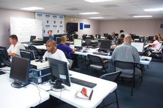 Local downtown residents works on projects, such as, resume development and job searching, at The Larson Training Center, a community learning facility located downtown, Wednesday July 1, 2014.