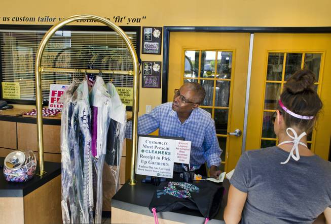 Mahamed Youssouf, owner of the Green Cleaners Alteration Center, calculates a customer's order on Wednesday, July 3, 2014. He is giving away 500 flags and cleaning flags for free in honor of the Fourth of July.