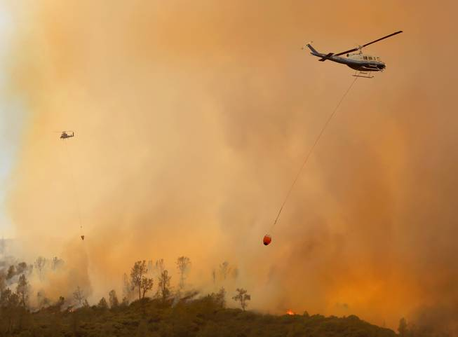 Private-hire helicopters make water drops on the Butts Fire above Snell Valley as the afternoon winds kicked up Wednesday, July 2, 2014, near Middletown, Calif.