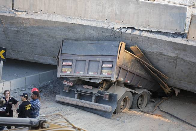 A truck is trapped underneath a collapsed bridge in Belo Horizonte, Brazil, Thursday, July 3, 2014. The overpass under construction collapsed Thursday in the Brazilian World Cup host city.