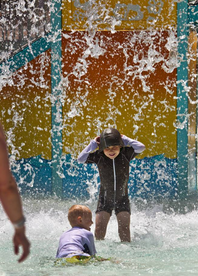 A bucket full of water is dumped on kids as they enjoy the Cowabunga Kids Cove during opening day at Cowabunga Bay on Friday, July 4, 2014.  L.E. Baskow