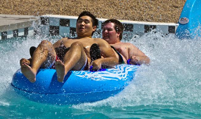 Elysian Fields and Andrew Huskey of Las Vegas complete the Point panic slide during opening day at Cowabunga Bay on Friday, July 4, 2014, in Henderson.