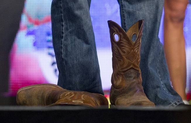Welterweight Kenny Robertson kicks off his cowboy boots during the UFC 175 weigh ins at the Mandalay Bay Resort on Friday, July 4, 2014.