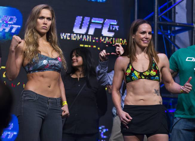 Ronda Rousey and Alexis Davis pose during the weigh-in for their UFC 175 bantamweight fight at Mandalay Bay on Friday, July 4, 2014.