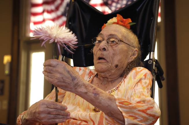 Gertrude Weaver holds a flower given to her a day before her 116th birthday at Silver Oaks Health and Rehabilitation Center in Camden, Ark., on Thursday, July 3, 2014. The Gerontology Research Group says Weaver is the oldest person in the United States and second oldest in the world.
