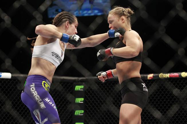 Ronda Rousey gets hit with a left by Alexis Davis during their fight at UFC 175 at the Mandalay Bay Events Center Saturday, July 5, 2014. Rousey retained her title with a 16-second TKO.