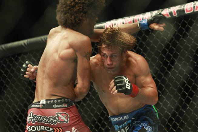 Urijah Faber ducks a punch thrown by Alex Caceres during their fight at UFC 175 at the Mandalay Bay Events Center Saturday, July 5, 2014. Faber won by submission in the third round.