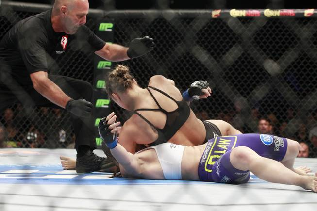 Referee Yves Lavigne steps in to stop Ronda Rousey as she pounds Alexis Davis during their fight at UFC 175 at the Mandalay Bay Events Center Saturday, July 5, 2014.