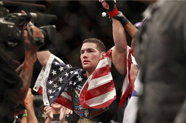 Chris Weidman raises his arms after defending his middleweight title against Lyoto Machida with a unanimous decision at UFC 175 at the Mandalay Bay Events Center Saturday, July 5, 2014.