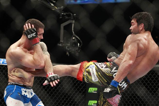 Lyoto Machida kicks Chris Weidman in the ribs during their fight at UFC 175 at the Mandalay Bay Events Center Saturday, July 5, 2014. Weidman won a unanimous decision to retain his middleweight belt.