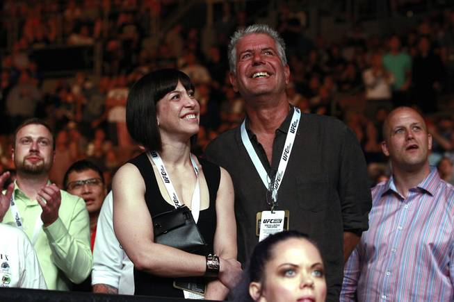 Chef, author and TV personality Anthony Bourdain and his wife Ottavia Busia smile between rounds of Chris Weidman's fight against Lyoto Machida during UFC 175 at the Mandalay Bay Events Center Saturday, July 5, 2014. Weidman won a unanimous decision to retain his middleweight belt.